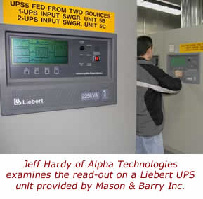 Jeff Hardy of Alpha Technologies examines the read-out on a Liebert UPS unit provided by Mason & Barry Inc.