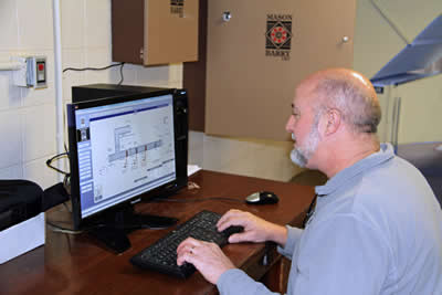 A Mason & Barry technician programs a customer's control system.